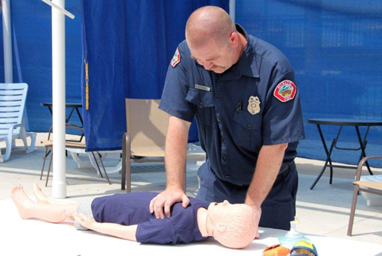 Fireman demonstrating CPR on dummy