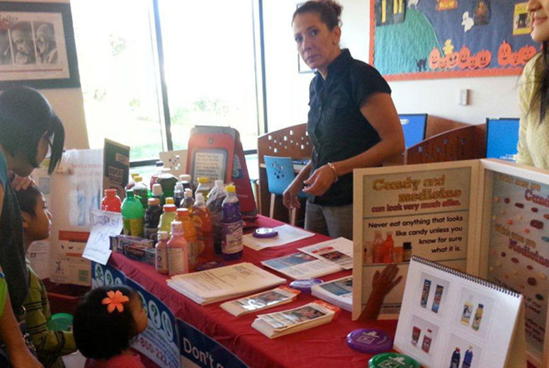 Woman standing behind poison prevention booth