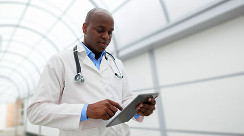 Male doctor reviewing tablet content while walking down medical center hallway
