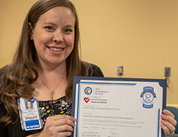 RN holding up certificate of recognition