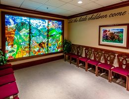 Interior of chapel with seating and stained glass image of Noah's Ark